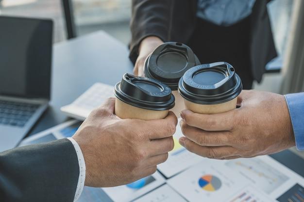 商談チームは、会議後、コーヒーカップを持って歓声を上げ、事業収入を増やすための戦略を立てます。