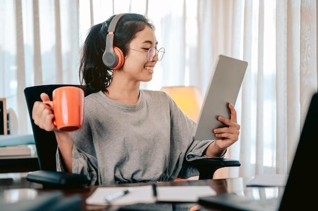 ヘッドフォンを身に着けているオレンジ色のカップからお茶を飲みながら自宅でシェアに座っている忙しい女性
