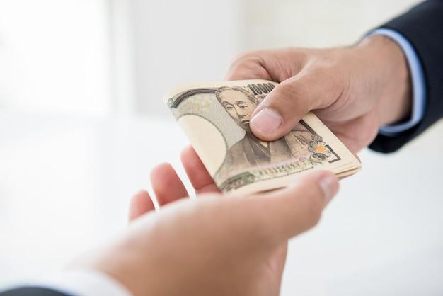 日本円のお金を彼のパートナーに渡すビジネスマン