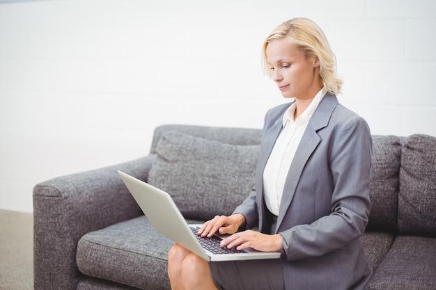 Bussinesswoman работает на ноутбуке, сидя на диване