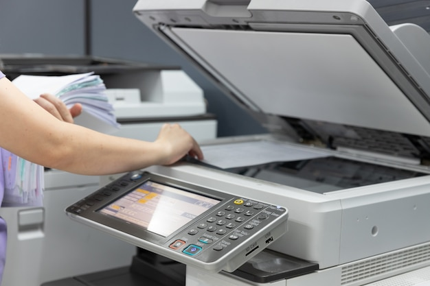 Bussinesswoman, используя копировальный аппарат для копирования документов.