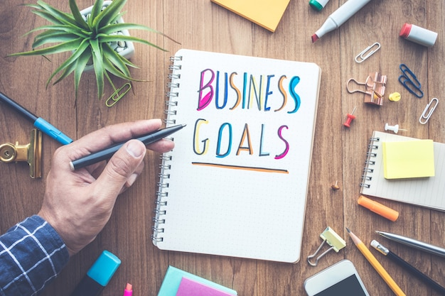Busuness goals message with male hand writing on notepad paper on wooden table and office supplies.business concepts.flat lay design