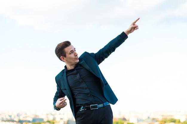 暗いスーツ、時計、黒シャツの若い深刻なbusunessmanが屋根の上に立つ
