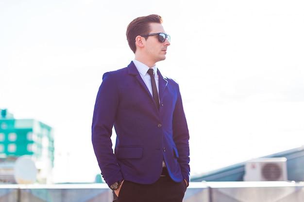 青いスーツとサングラスの若いbusunessmanは屋根の上に立つ