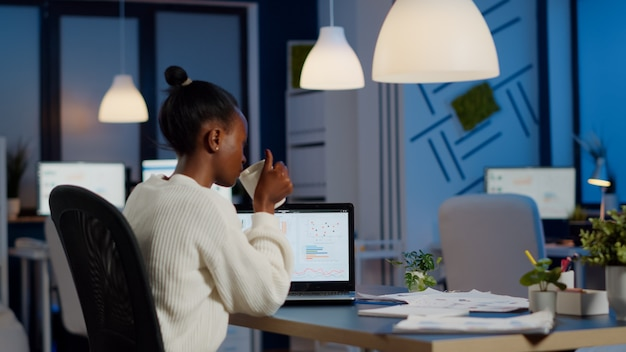 Busy african business woman analysing financial reports checking company statistics graphs, looking at laptop, pointing to numbers late at night in start-up office doing overtime to respect deadline