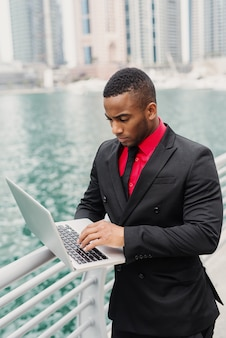 Busy afro-american businessman standing in port and looking through some documents on his laptop.