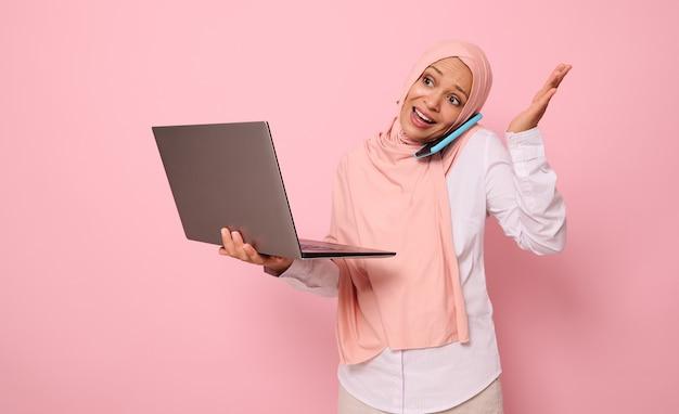 바쁘고 어리둥절한 이슬람 아랍 여성은 히잡을 쓰고 비즈니스 스마트 캐주얼을 입고 노트북을 들고 휴대전화로 이야기하고 손으로 몸짓을 합니다. 복사 공간이 있는 분홍색 배경 위에 절연