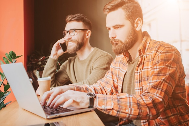忙しくて真面目なビジネスマンがカフェで目覚めています。そのうちの1人はコンピューターで作業しており、もう1人は電話で話している。