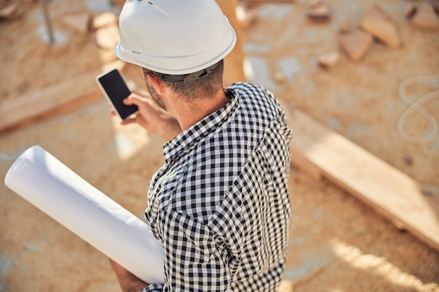 設計図と電話のロールを持つ忙しい建築家