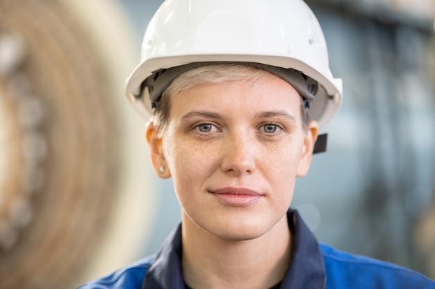 Занят азиатский оператор с чпу в оранжевом шлеме работает на панели управления автоматизированного станка на заводе