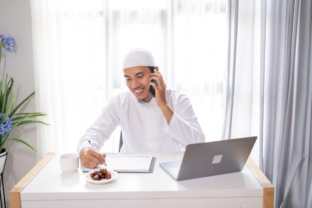 바쁜 아시아 회교도 사업가 자신의 휴대 전화를 사용하여 전화를