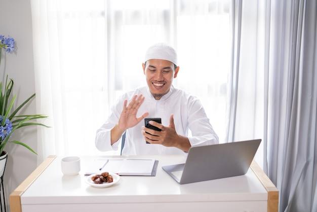 바쁜 아시아 무슬림 사업가 자신의 휴대 전화를 사용하여 화상 통화를