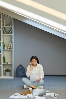 床に足を組んで座って、電話でグループメートと大学の仕事について話し合っている忙しいアジアの学生の女の子