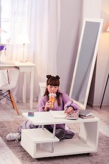 家で忙しい。レモンと水を飲みながらメモをとる気配りのある子供