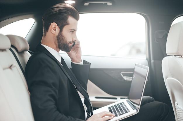 Занят на работе. уверенный молодой бизнесмен работает на своем ноутбуке и разговаривает по телефону, сидя в машине