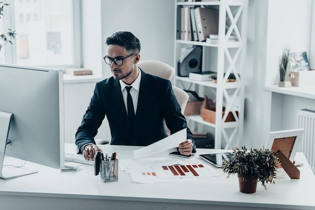 Занят на работе. красивый молодой человек в полном костюме, работающий с документами