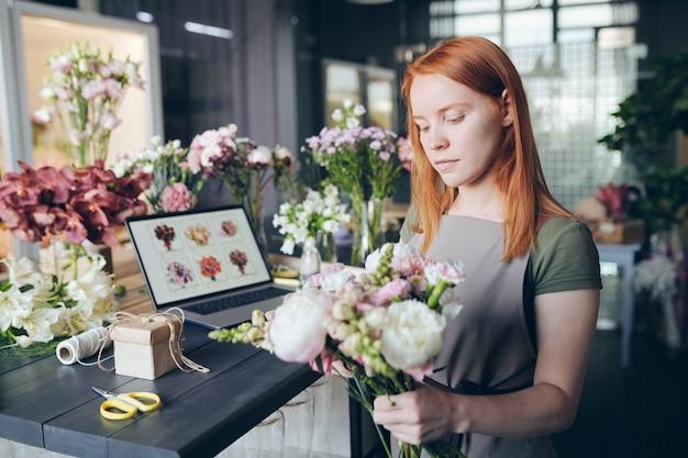 꽃 가게에서 일하는 동안 꽃과 장식 도구로 가득한 카운터에 서서 꽃다발에 꽃을 섞는 앞치마에 바쁜 매력적인 소녀