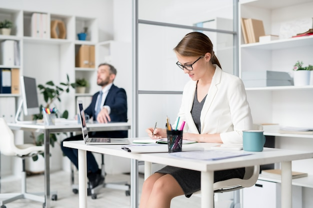 Busy attractive lady planning schedule in office