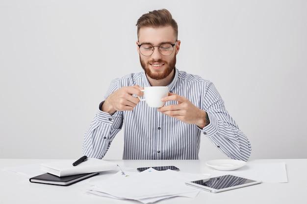 Impegnato uomo attraente con folta barba ha una pausa caffè, si siede al posto di lavoro, lavora con i documenti