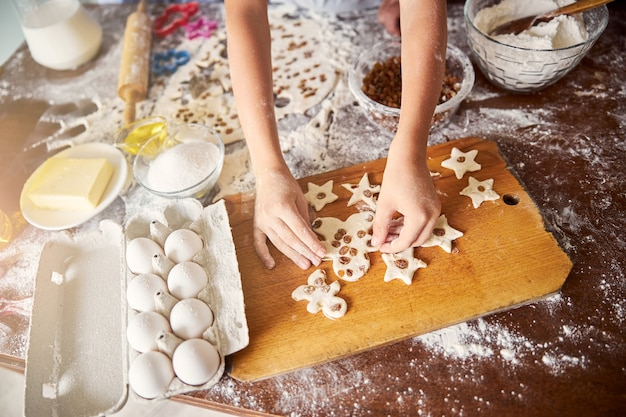 Busy baker arranging star-shaped dough on the table