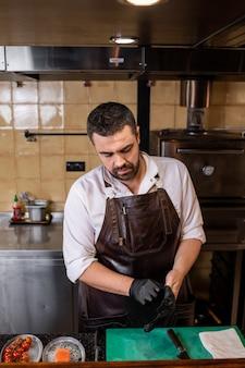 Занятый бородатый повар в кожаном фартуке стоит у стойки и надевает перчатки перед приготовлением