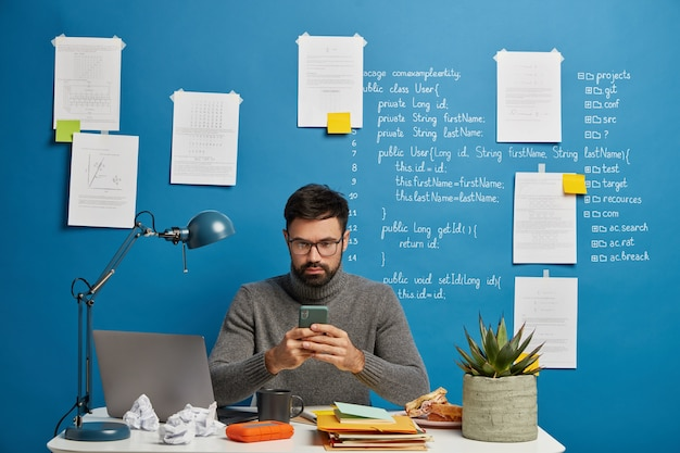 Busy bearded male programmer ponders on task, concentrated into smartphone, wears optical glasses, prepares for conference