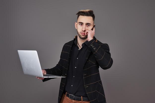 스마트 폰으로 얘기하고 회색 배경 위에 손에 커피 한잔 들고 노트북 컴퓨터를 사용하는 비즈니스 옷에 바쁜 수염 된 남자.