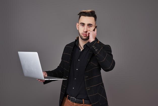 스마트 폰으로 얘기하고 랩톱 컴퓨터를 사용하여 비즈니스 옷을 입고 바쁜 수염 난된 남자