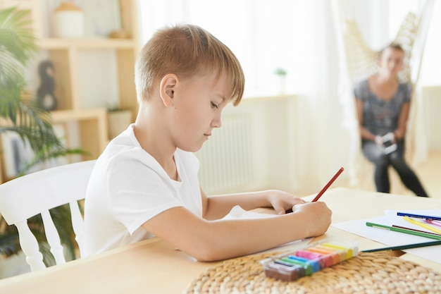 Busy boy of preteen age sitting at home with colorful plasticine on wooden table, using pencil, concentrated on creative process. horizontal image of caucasian little artist painting, doing homework