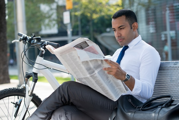Busy broker analyzing news resting in park