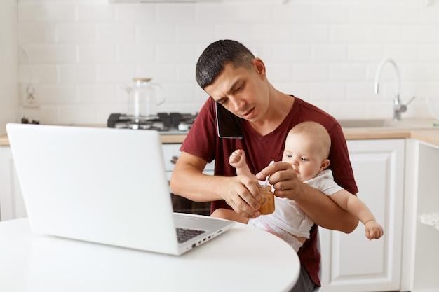 マルーンカジュアルスタイルのtシャツを着て、キッチンのテーブルに座って、幼児の娘にフルーツピューレを与え、ビジネスパートナーと携帯電話で話している忙しいブルネットの男性。