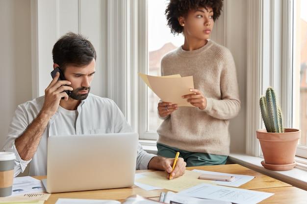 忙しいビジネスパートナーは素晴らしい結果を得るために一生懸命働いています。真面目な男が電話で会話