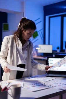 Busy business woman looking on financial reports, checking statistics graphs standing at desk late at night in start-up office