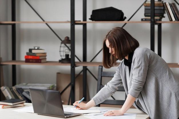 オフィスの机の近くに立っている忙しいビジネスウーマン