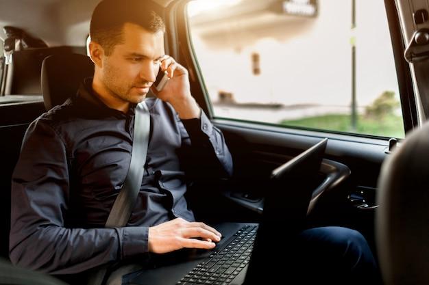 タクシーで忙しいビジネスマン。マルチタスクの概念。乗客は後部座席に乗り、同時に働く。スマートフォンで話し、ラップトップを使用する