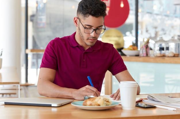 Un uomo d'affari impegnato indossa occhiali e maglietta, scrive informazioni nel blocco note, prepara idee per il progetto di avvio, beve caffè e mangia croissant, posa in un bistrot contro il muro sfocato.