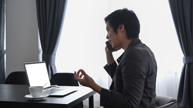 Занят бизнесмен работает с ноутбуком и разговаривает по мобильному телефону в офисе.