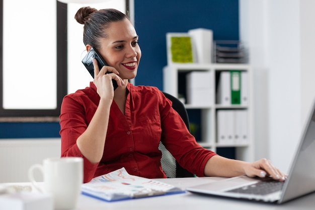 Busy businesswoman answering phone call sitting at desk in corporate workplace