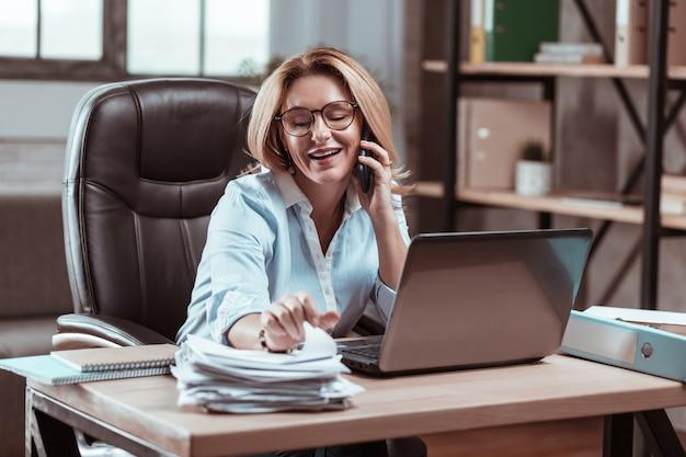 忙しい実業家。パートナーと電話で話す忙しい魅力的な経験豊富なビジネスマン