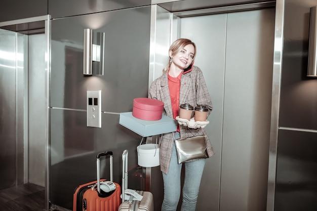 Занятая деловая женщина. деловая женщина, стоящая возле багажа, зовет своего парня, ожидающего его возле лифта