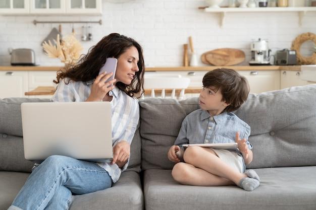 Занятый бизнесвумен мать работает дома, разговаривает с ребенком с ноутбуком на коленях, звонит по телефону на диване