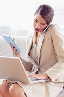 Busy businesswoman sitting on sofa multi tasking