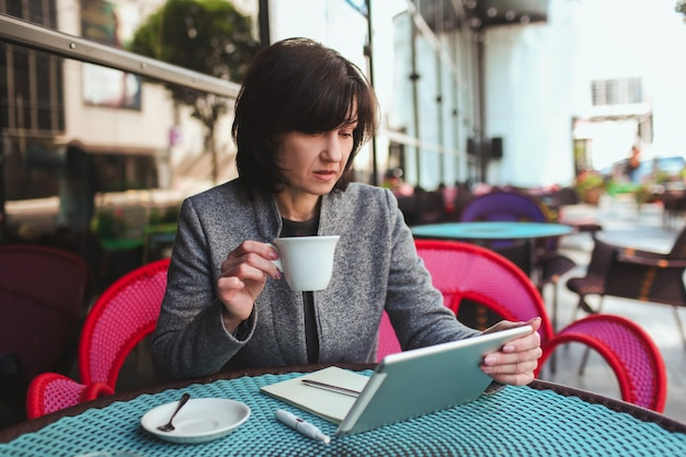 タブレットの画面を見てお茶を一杯飲む忙しい穏やかで平和な実業家