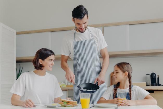 바쁜 돌보는 아버지는 아내와 딸을 위해 맛있는 아침 식사를 준비하고 앞치마를 입고 튀긴 계란을 접시에 넣습니다.