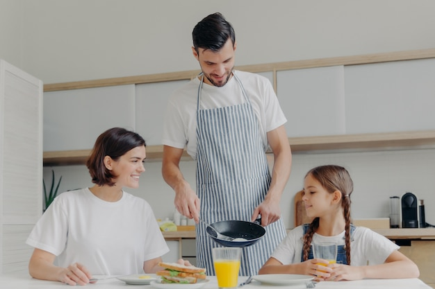 Busy caring father prepares delicious breakfast for wife and daughter, wears apron, puts fried eggs on plate.