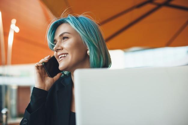 커피 숍에서 컴퓨터와 함께 휴식하는 동안 전화 토론을하는 파란 머리를 가진 바쁜 백인 기업가