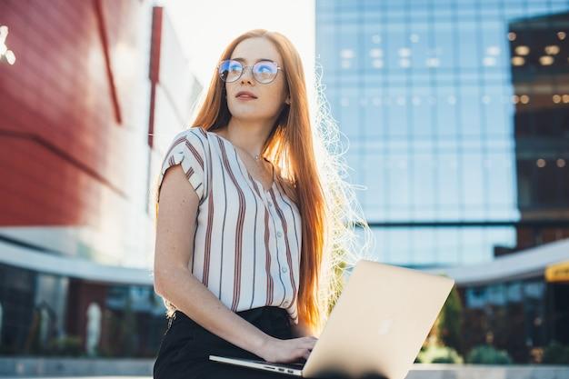 眼鏡をかけ、外のラップトップで働いている髪とそばかすを読んで忙しい白人起業家