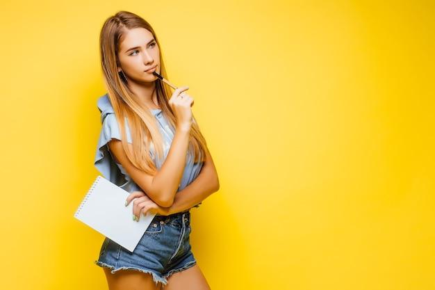 Impegnata affascinante donna attraente che scrive note sul blocco note che indossa una maglietta blu alla moda ed elegante isolata sul muro giallo