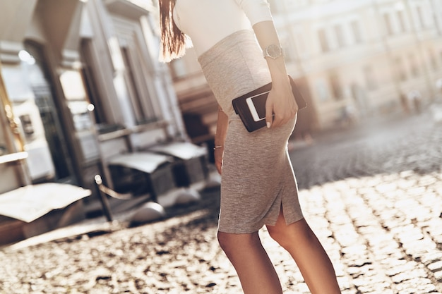 Busy in the city. close-up of young woman carrying her smart phone and wallet while walking outdoors
