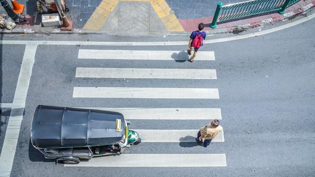 Занятые толпы жителей города проходят пешеходный переход